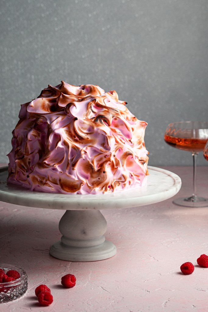 A torched bake alaska covered in pink meringue beside two glasses of rose