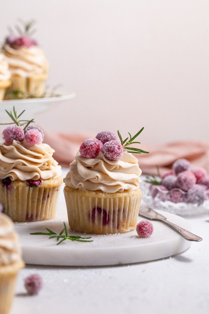 A cranberry cupcake topped with piped frosting is garnished with candied cranberries , sitting on a marble plate