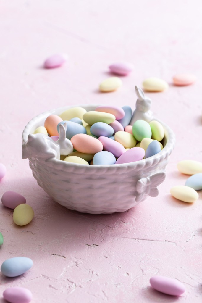 A small white bowl decorated with small rabbits and a butterfly is filled with pastel Easter candies