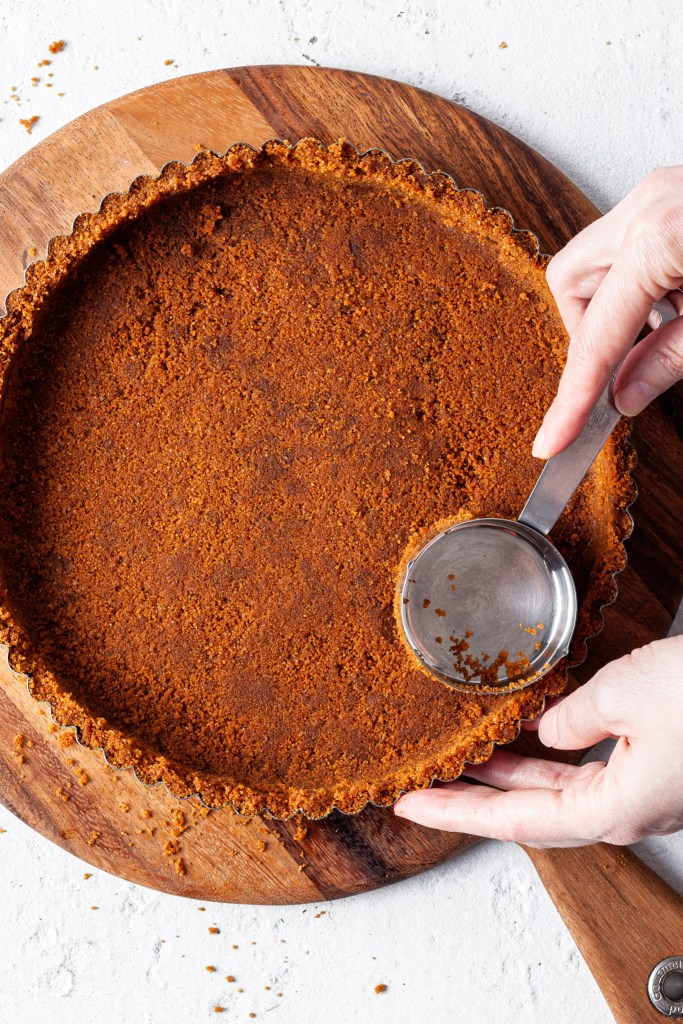 Hands using a measuring cup to press a cookie crumb crust into a tart pan.