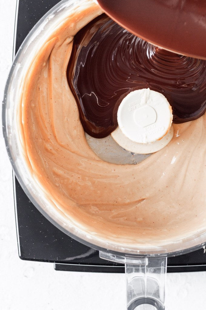 View into a food processor where melted chocolate is being added to the tofu and cookie butter mixture.