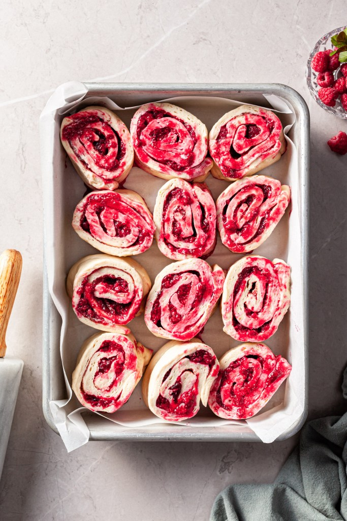 Raspberry sweet rolls in a baking pan ready to be baked.