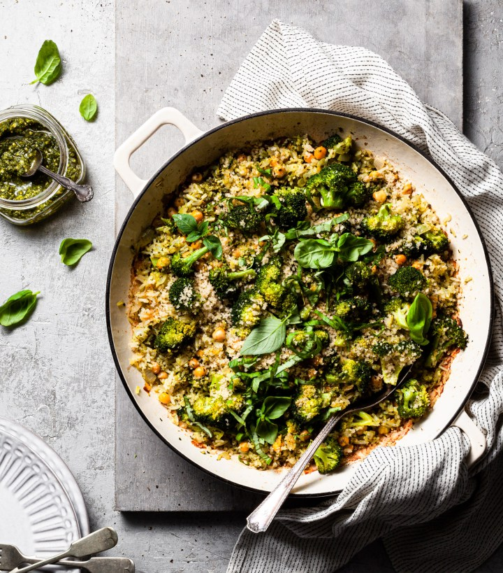 A white cast iron skillet filled with pesto baked broccoli and rice.