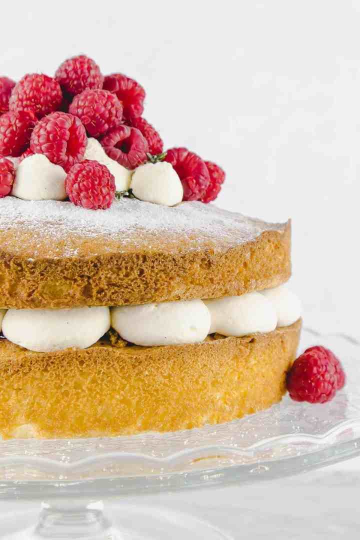 Close up of raspberry Victoria sponge with fresh cream between the cake layers