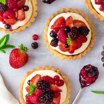 Top down view of pastry tarts, filled with cream and summer fruits. Scattered strawberries and blackcurrants on the table.