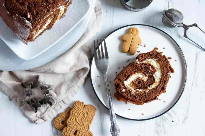A slice of chocolate and gingerbread roulade cake on a plate with a gingerbread man