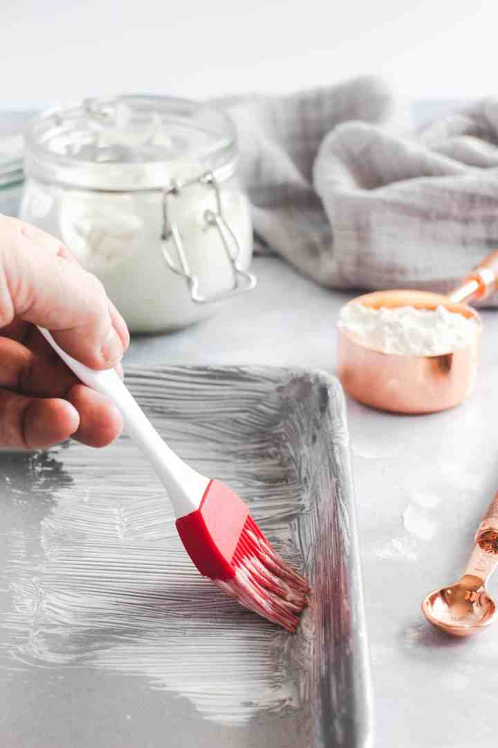 Red pastry brush coating a baking pan with cake grease