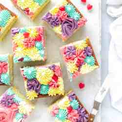 Vanilla sheet cake cut into square slices
