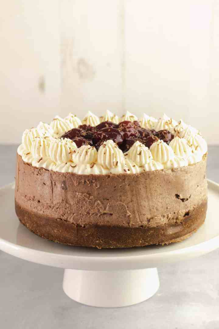 Chocolate cheesecake on a white cake stand with whipped cream topping and black cherries