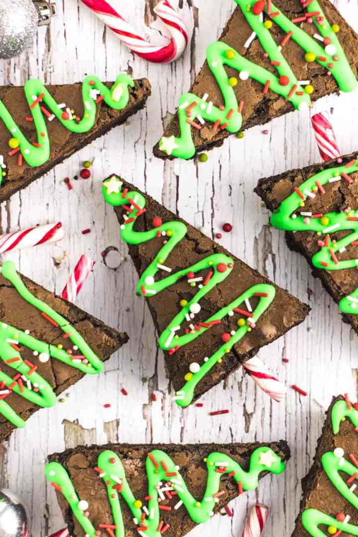 Brownies cut into triangles decorated with green icing, sprinkles and candy canes