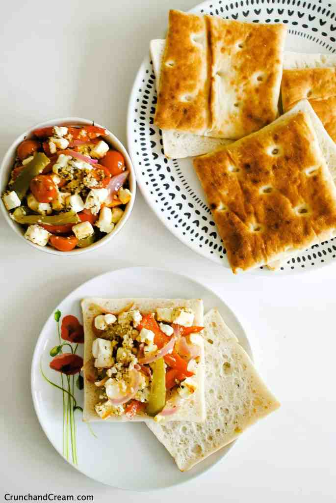 overhead of a bowl of roasted feta salad with peppers, onions and tomatoes with a plate of bread rolls. One roll is open and topped with the feta salad