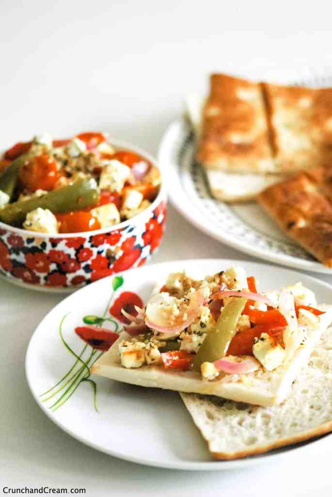 an open sandwich with roasted pepper, tomato and onion feta salad spread on it. behind it is a bowl of the salad and more bread rolls
