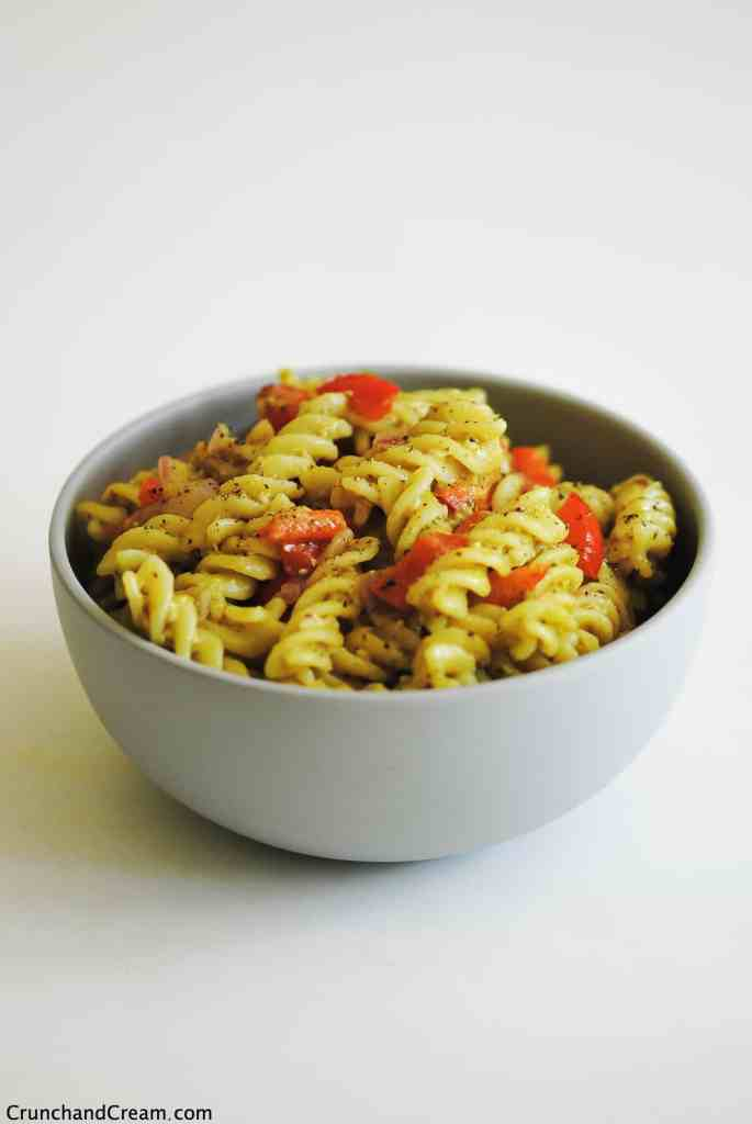 a bowl of pesto pasta with diced red pepper on a white background