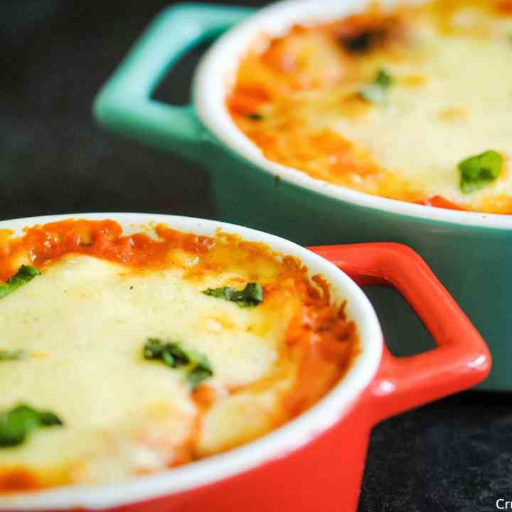 2 individual casserole dishes full of baked rice in a tomato sauce topped with melted cheese