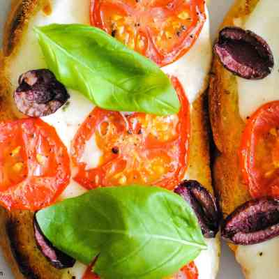 close-up of toast topped with melted mozzarella, sliced tomatoes, halved olives and basil leaves