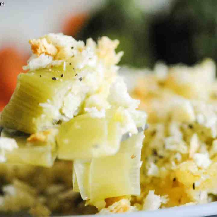 a forkful of creamy, cheesy leeks with steamed veggies in the background