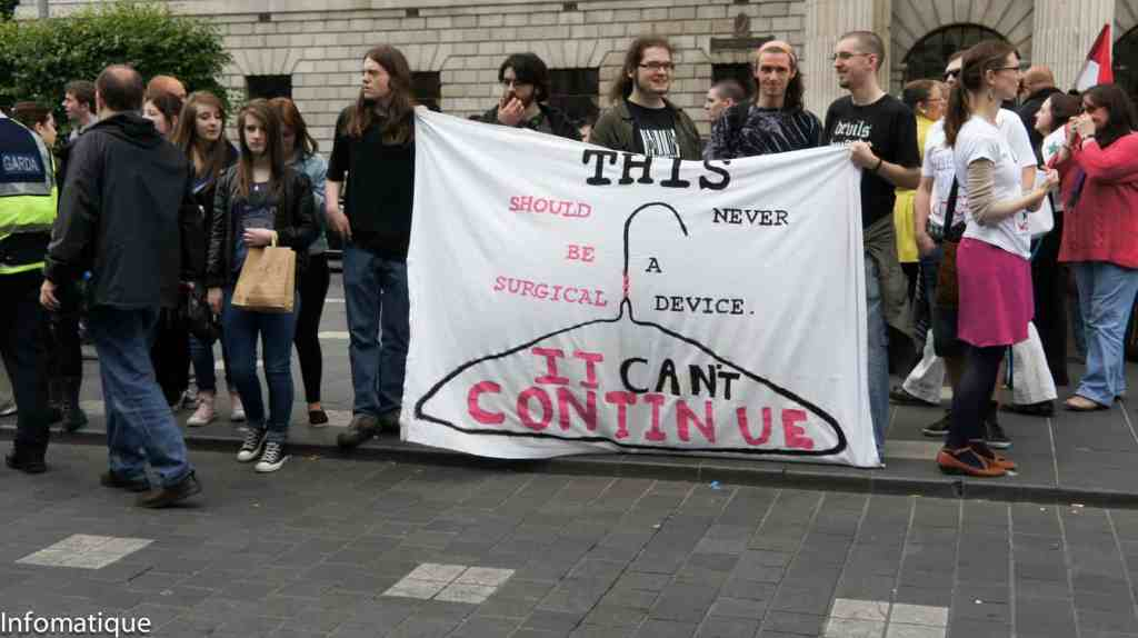 """Activists at a Pro Choice rally hold a sign that reads """"THIS CAN'T CONTINUE"""" with drawing of a wire hanger."""
