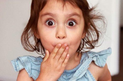 Petite fille qui a l'air surprise avec la main sur la bouche.
