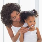 Mother improves child's oral health by helping young daughter brush her teeth