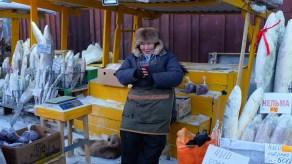 A fishmonger in a rabbit skin hat in Yakutsk, Russia.
