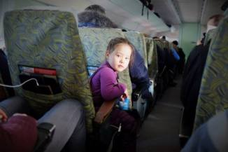 Flying on a Soviet-era plane in Russia's Sakha Republic in the dead of winter, a local girl turns around in her seat to check out the curious foreigner.