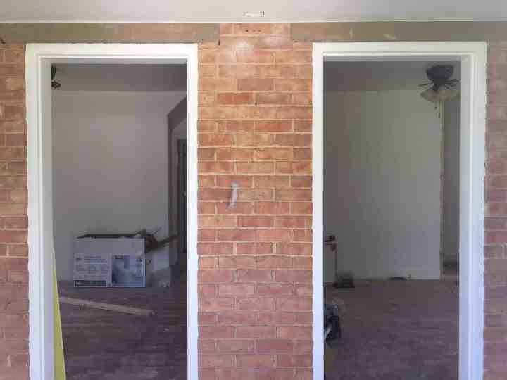 Two front doors looking into living area surrounded by brick exterior. No doors are installed.