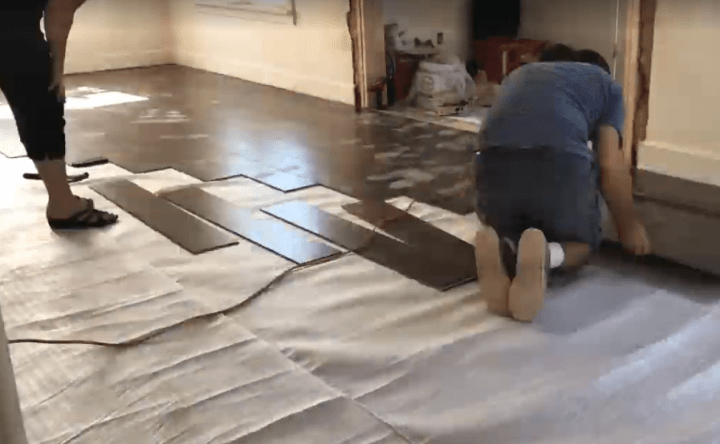 Image of dark brown laminate flooring being installed