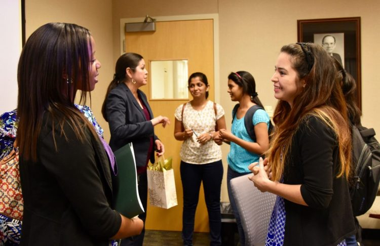 Romelia's daughter (front right) speaking with a UT Dallas PhD student. In the Foreground you can see Romelia speaking with two UT Dallas CS students.