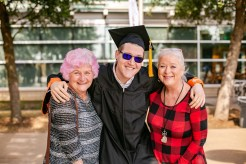 Peter Brehm is flanked by his aunt, Julia James (right), and spunky grandmother, Mary Brehm, who used pink shampoo to spice up Peter's graduation from UTD with a Bachelor of Science in computer science.