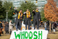 Manan Lakhani, Nikhil Kadel and Karan Motani (left to right) stand tall and throw their caps in the air in celebration of earning their master's degrees in computer science.