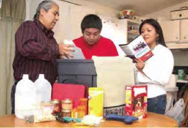 A NAtive American family around a kitchen table packing supplies in an emergency kit