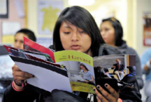 A shot of an ethnic student reading college brochures