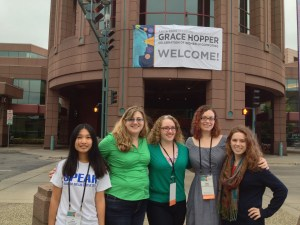 Ginny Huang '14, Professor Sara Sprenkle, Sam O'Dell '15, Cory Walker '15, and Camille Cobb '12 pose outside the Minneapolis Convention Center, under the Grace Hopper sign.