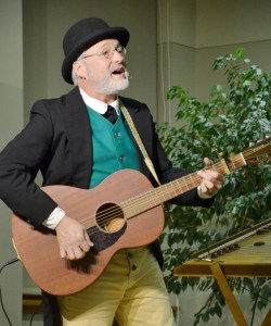 Folk musician Paul Siebert play a song Monday evening in the Sandoz Center Chicoine Atrium. — Photo by Spike Jordan