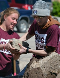 In 2017: Caitlin Gustafson, left, 20, sophomore of Seward, hands Dominic Badura,19, freshman of Omaha, a rock Saturday as part of the fifth annual The Big Event. —Photo by Jordyn Hulinsky