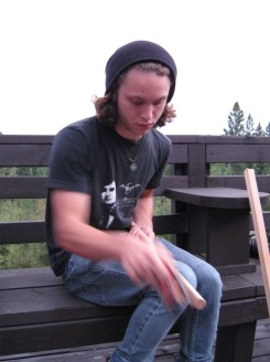 Dylan carves his cedar sticks with speed.