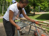 Miranda works on smoothing one of our balsam push-poles.