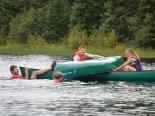 Zane and Alex prepare to flip a canoe