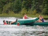 Zane and Alex prepare to flip a canoe