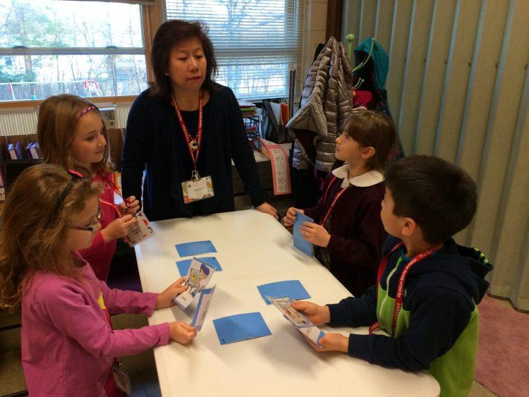 Teacher teaching elementary school children with cards.