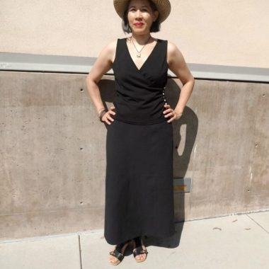 Asian woman wearing balck skirt and to with straw sun hat