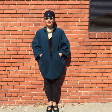Asian woman wearing teal green wool coat standing in front of brick wall with hands in pockets, wearing a black hat and white sunglasses