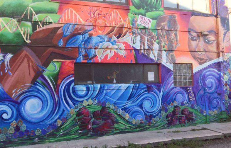 Mural painted on a wall - blue waves people and people in community above promoting health