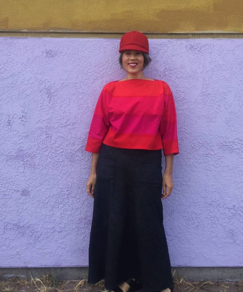 Asian woman standing in front of white wall wearing Suri top in bright orange and hot pink and denim skirt.