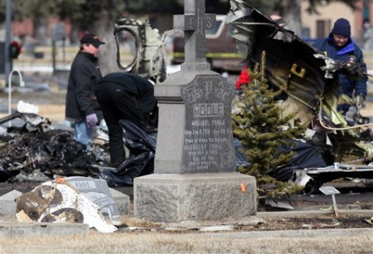 Debris from the tail section of a plane is seen in the foreground as NTSB investigators and local authorities examine the scene at Holy Cross Cemetery, where a plane crashed killing 14 people on Sunday, adjacent to the Butte Airport in Butte, Mont., on Tuesday, March. 24, 2009. (AP Photo/Mike Albans)