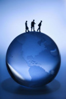 Figurines walking atop blue globe on blue background.