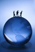 Figurines walking atop blue globe on blue background.