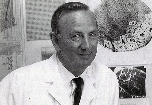 Gordon Lennox with a photomicrograph of a cross-section of a wool fibre in the background (taken in 1970)