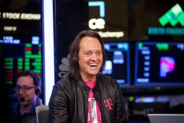 John Legere, PDG de T-Mobile, souriant lors d'une interview au New York Stock Exchange.