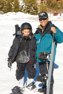 (U.S. Air Force photo/Stacy Foster) Col. Cary Chun and his son Ian take a break from snowboarding to pose for a photo here Jan. 30. Military members, family and friends converged on the resort for three days of skiing, snowboarding, tubing and more Jan. 30 through Feb. 1. Colonel Chun is the 50th Space Wing commander at Schriever Air Force Base, Colo.